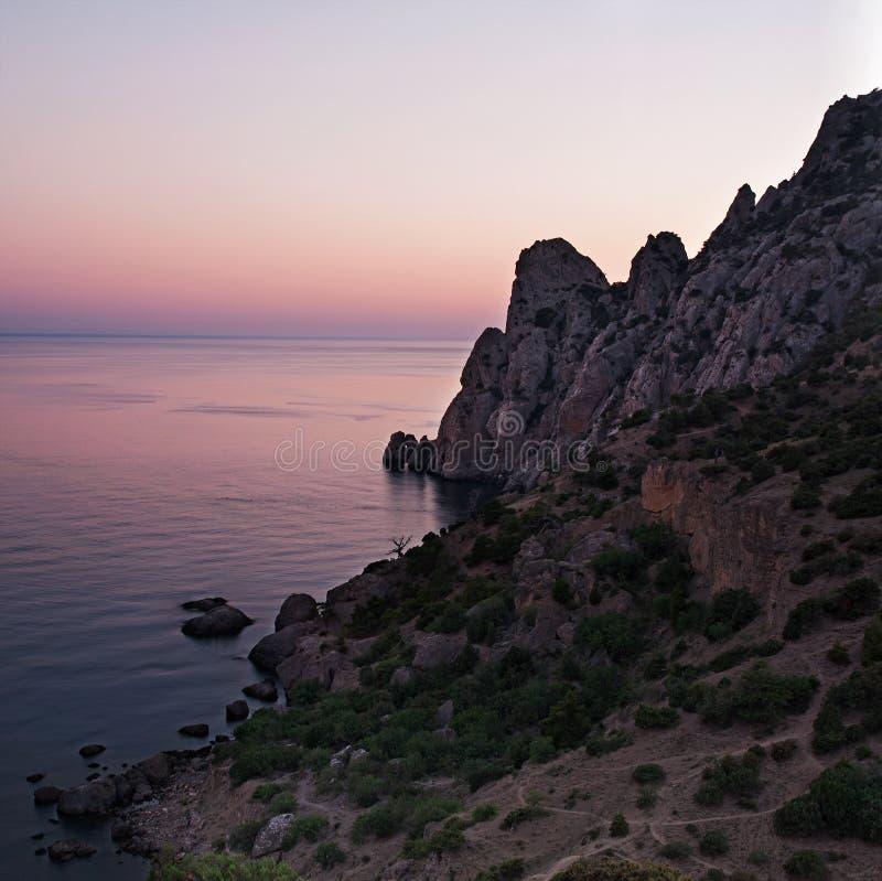 De mening van Blauwe baai en zet karaul-Oba bij zonsondergang op stock foto