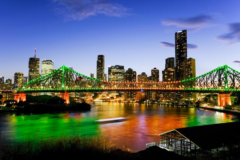 De mening van Brisbane stak omhoog bij schemer met een veerboot aan die onder de Verhaalbrug overgaan stock fotografie