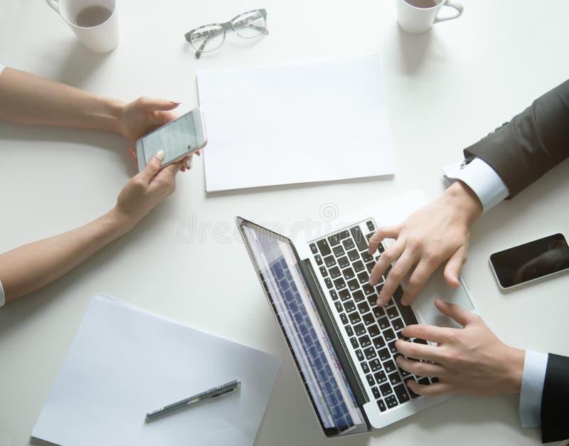 De mening van de bureaudesktop, wijfje over telefoon, mannetje over laptop stock afbeeldingen