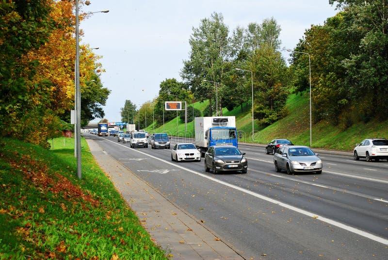 De mening van de de straatherfst van Ukmerges van de Vilniusstad met auto's en vrachtwagens royalty-vrije stock foto