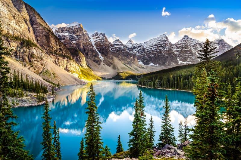 De mening van de landschapszonsondergang van het meer en de bergketen van Morain stock afbeeldingen