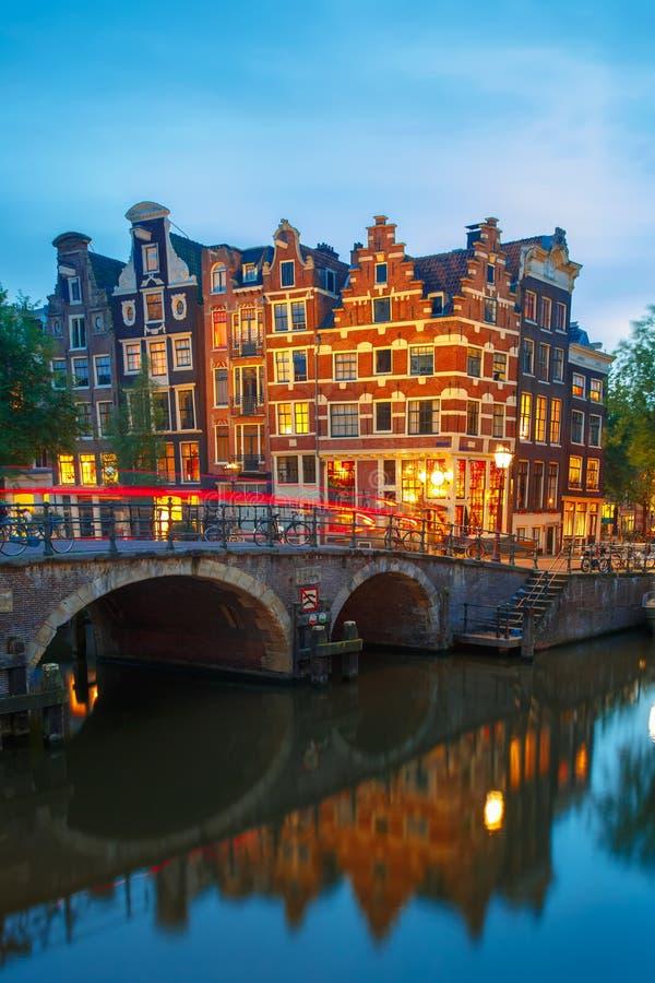 De mening van de nachtstad van het kanaal en de brug van Amsterdam stock foto