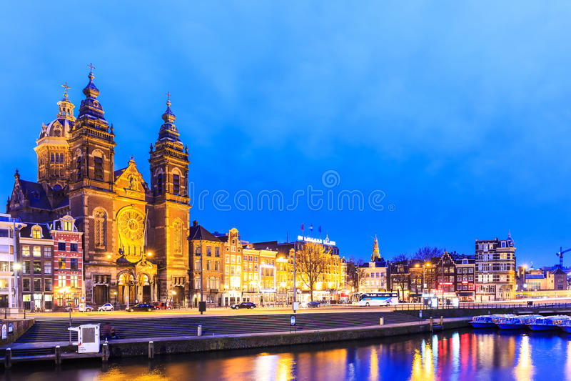 De mening van de nachtstad van het kanaal van Amsterdam en Basiliek van Heilige Nichola stock afbeeldingen