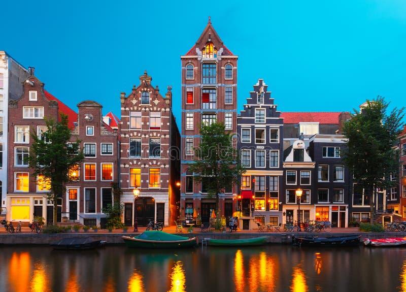De mening van de nachtstad van het kanaal van Amsterdam met Nederlandse huizen stock fotografie