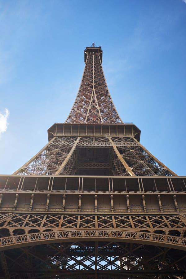 De mening van de detailbodem van de Toren van Eiffel op de blauwe hemelachtergrond in zonsonderganglicht stock afbeeldingen