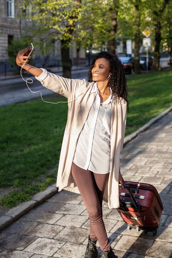 De mening van gemiddelde lengte bij de modieuze Afrikaanse vrouw met mooie glimlach die de koffer houden en selfie op mobiel neme stock fotografie