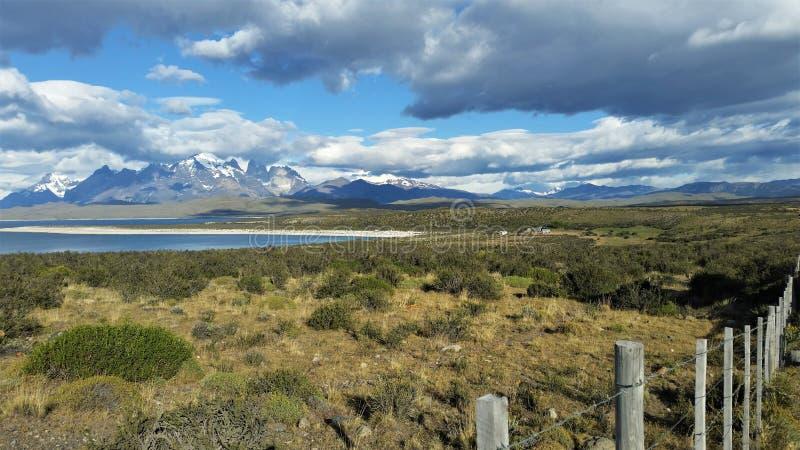 De mening van graniet snow-capped pieken schrobt erachter gebied en saffier blauw meer in Patagonië, Chili stock foto