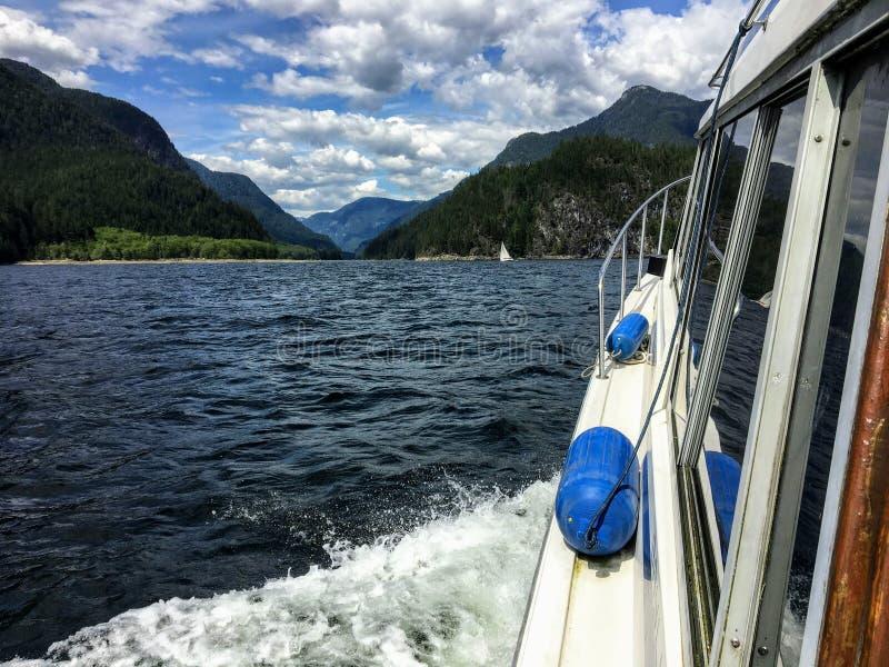 De mening van de havenkant van een powerboat aangezien het zich langs het oceaanwater van een mooie verre inham beweegt royalty-vrije stock afbeelding