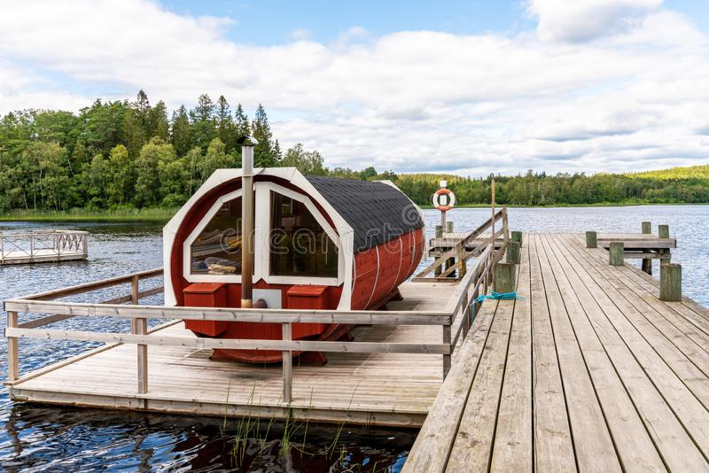 De mening van het de aardlandschap van het de zomermeer van een traditioneel Skandinavisch water die rode houten sauna spa drijve stock afbeelding