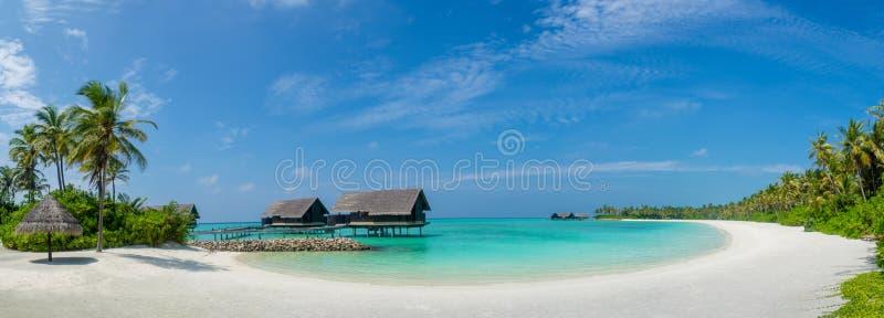 De mening van het het strandpanorama van de Maldiven met blauwe oceaan en hemel dichtbij villa's royalty-vrije stock fotografie