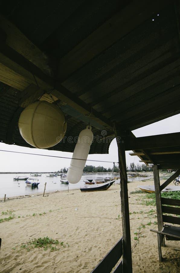De mening van het strandlandschap van binnenuit vissersplattelandshuisje met het witte en gele boei hangen royalty-vrije stock afbeelding