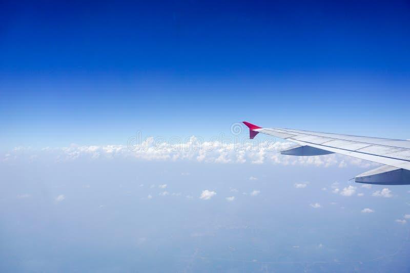 De mening van het vliegtuigvenster met blauwe hemel en wolken royalty-vrije stock afbeelding