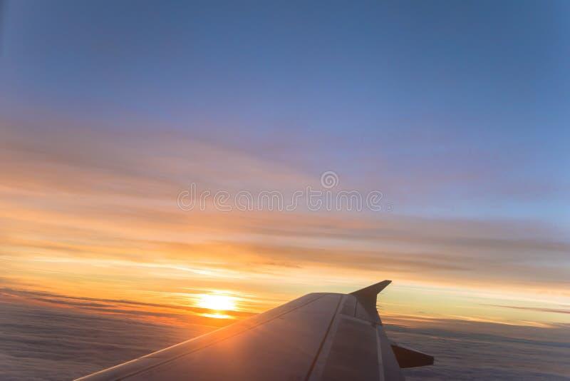 De mening van het vliegtuigvenster van vliegtuigvleugel en zonsopgangzonsondergang over oranje en blauwe hemel stock foto's