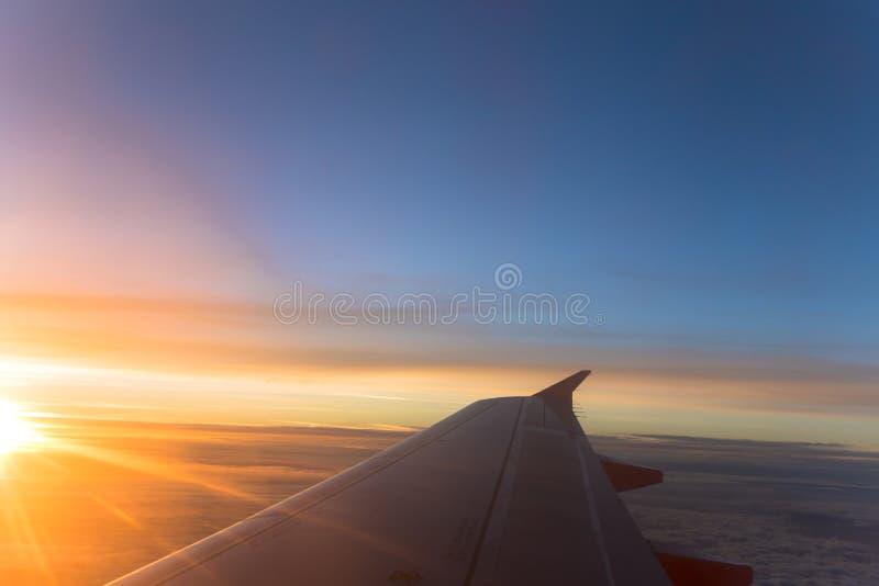 De mening van het vliegtuigvenster van vliegtuigvleugel en zonsopgangzonsondergang over oranje en blauwe hemel stock afbeelding