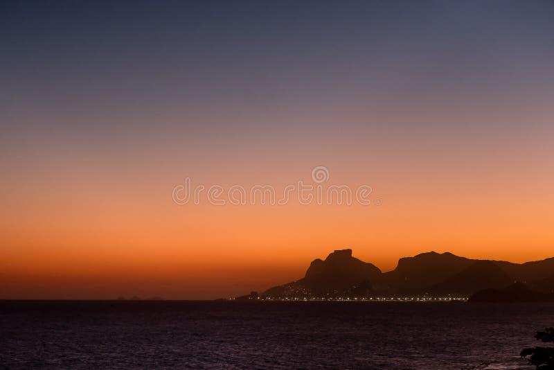 De mening van het zonsondergangsilhouet van Gavea-Steen in Rio de Janeiro van Itacoatiara-strand wordt gezien dat Niteroi, Rio de stock afbeelding