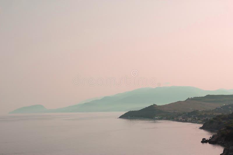 De mening van de hoogte van de berg in het overzees bij zonsondergang royalty-vrije stock afbeeldingen