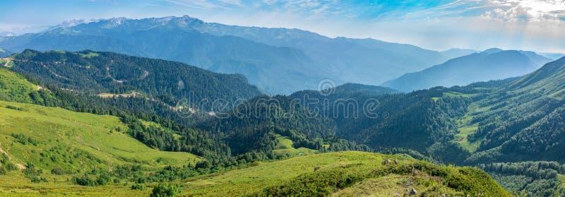 De mening van de hoogte van de groene die bergvallei met een kabelwagen, door hooggebergte wordt omringd Snow-capped bergpieken stock foto