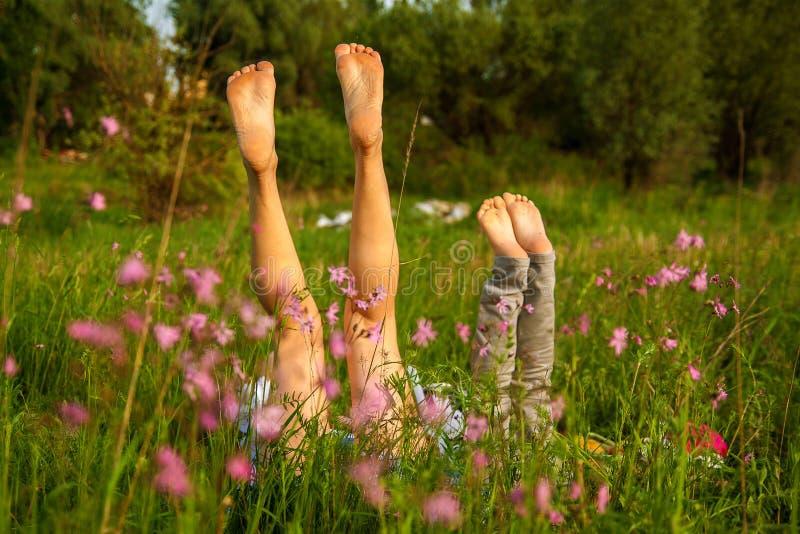 De mening van jonge moeder en dochter op groene grasachtergrond Voeten close-up stock foto