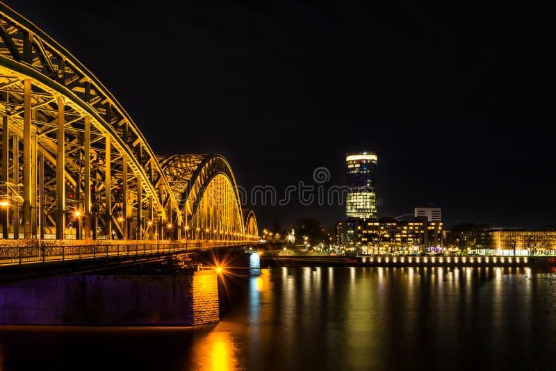De mening van Keulen aan Deutz bij de rivier Rijn en Hohenzollern leidt brug bij nacht op royalty-vrije stock afbeeldingen