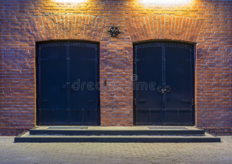 De mening van de nacht Zaken - de Horizon van de Stad van Nietjes Twee grote metaaldeuren in een rood baksteengebouw De ingang aa stock foto's
