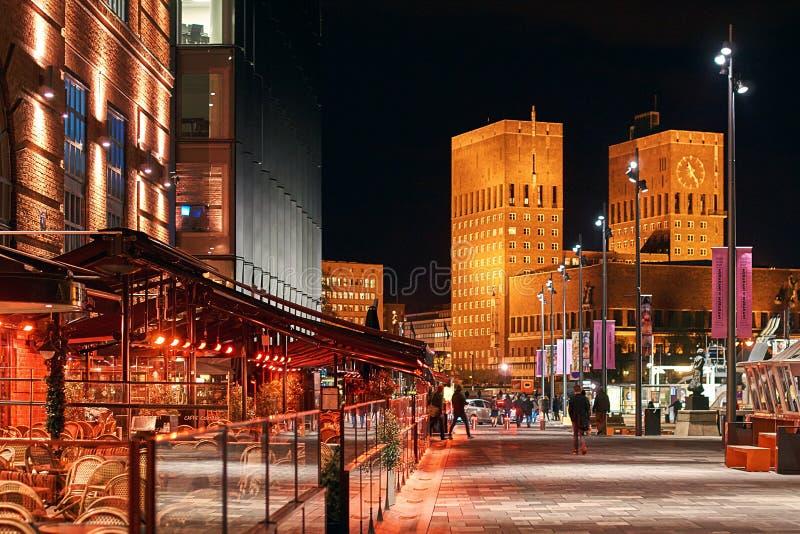De mening van de nachtstad van Oslo, Noorwegen bij het Dok van Aker Brygge met restaurants en Stadhuis of Radhuset op achtergrond stock afbeeldingen
