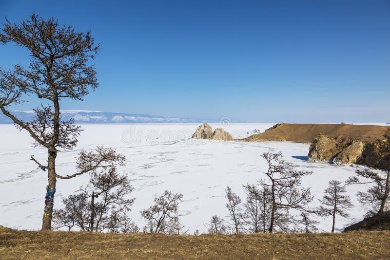 De mening van Olkhon-eiland op meer Baikal, Shamanka-rots en Kaap Burkhan in de winter zonnige dag Het gebied van Irkoetsk, Ooste royalty-vrije stock afbeeldingen
