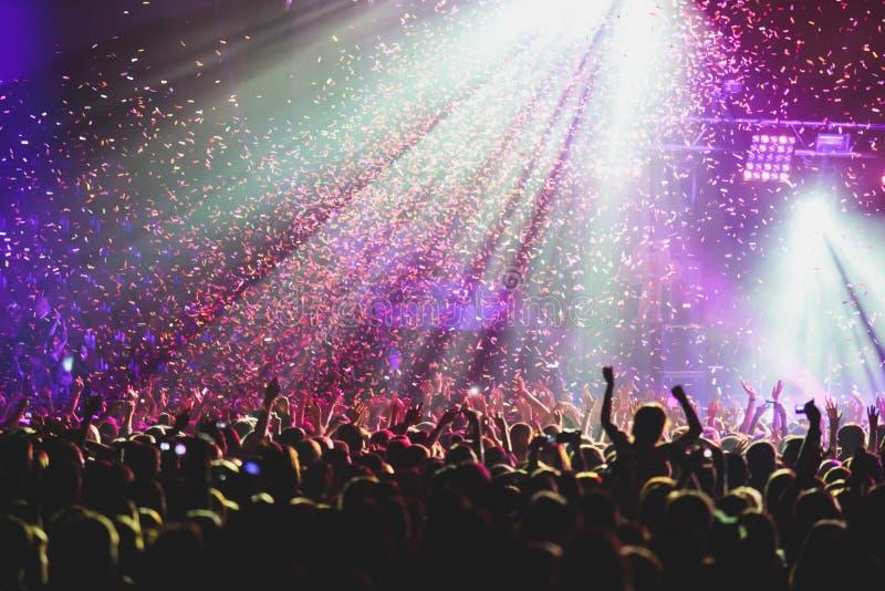 De mening van rotsoverleg toont in grote concertzaal, met menigte en de stadiumlichten, een overvolle concertzaal met scènelichte stock fotografie