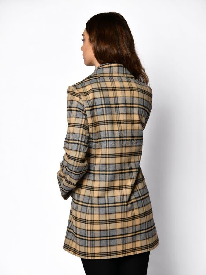 De mening van de rug Het jonge mooie vrouw stellen in gecontroleerd manier toevallig jasje stock afbeelding