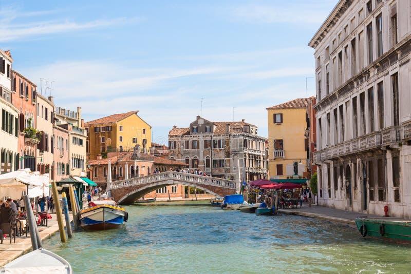 De mening van de straat van Venetië, de kleurrijke huizen en het kanaal met boten en Guglie overbruggen in Venetië zonnige dag, I royalty-vrije stock afbeelding