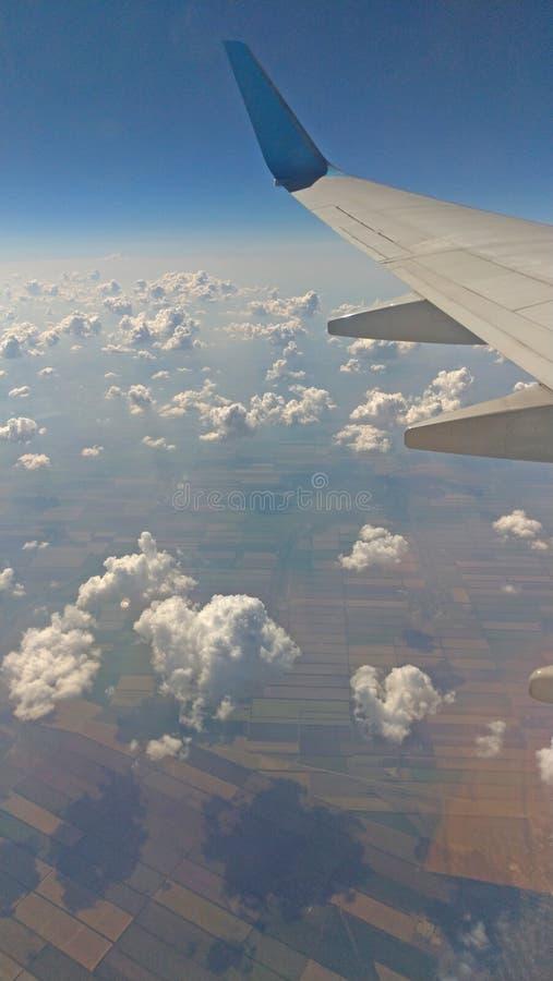 De mening van de vliegtuigvleugel uit het venster op de bewolkte hemelachtergrond De achtergrond van de vakantievakantie Vleugel  royalty-vrije stock fotografie