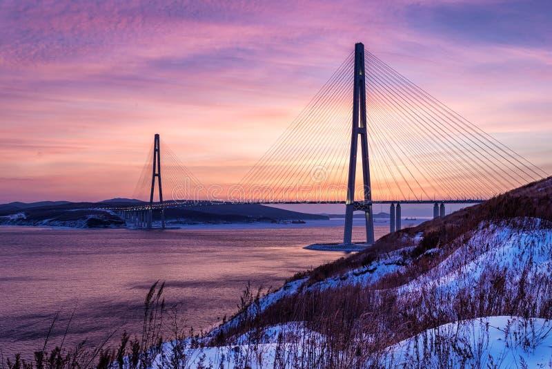 De mening van de de winterzonsondergang van lange kabel-gebleven brug in Vladivostok, Rusland stock foto