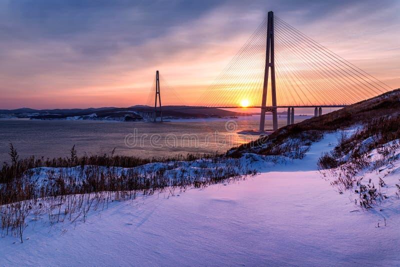 De mening van de de winterzonsondergang met verse sneeuw en lange kabel-gebleven brug in Vladivostok, Rusland royalty-vrije stock fotografie