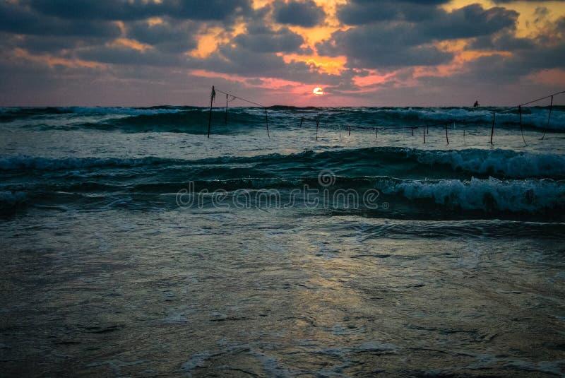 De mening van de de zomerzonsondergang van een strand onder een dramatische bewolkte hemel royalty-vrije stock foto