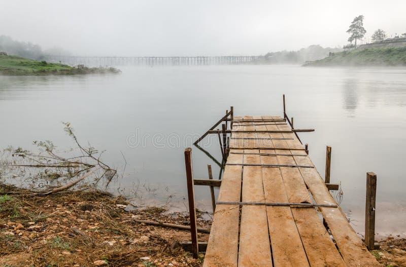 De menings oude houten brug in rivier met mist stock afbeeldingen