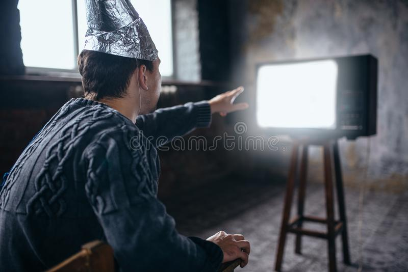 De mens in aluminiumfoliehelm bereikt TV stock fotografie
