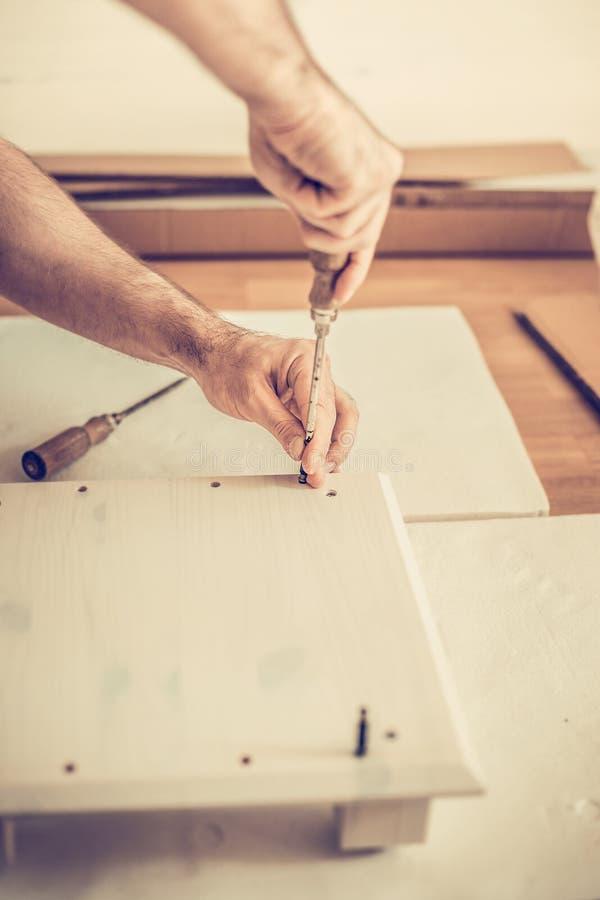 De mens assembleert meubilairgarderobe, verdraait schroeven in de groeven, meubilairassemblage royalty-vrije stock foto