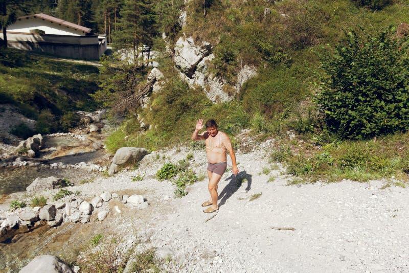 De mens baadt in de dalingen van een bergstroom op de stenen in aard royalty-vrije stock foto