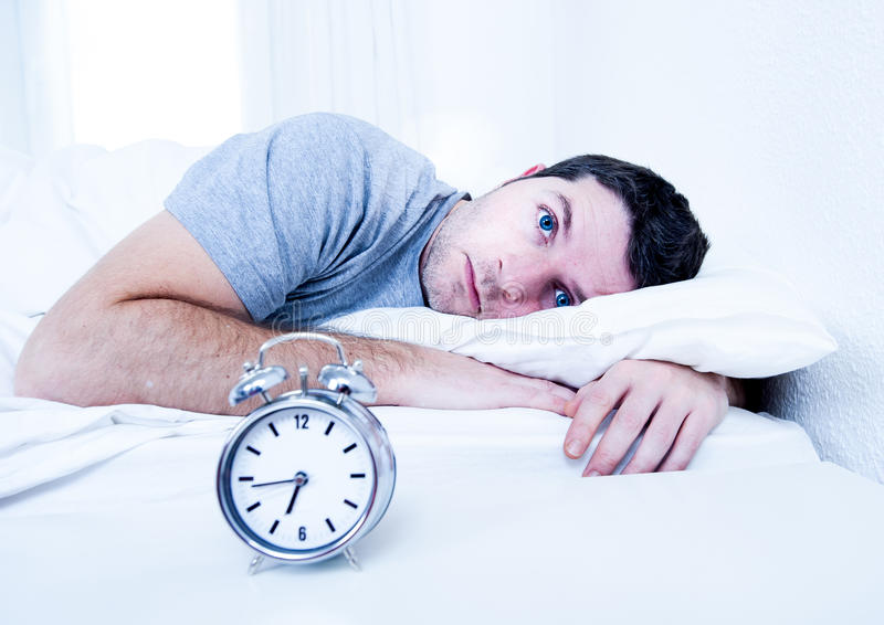 De mens in bed met ogen opende het lijden van aan slapeloosheid en stock fotografie