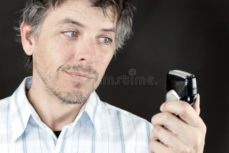 De mens bekijkt in Elektrische Raxor stock afbeelding