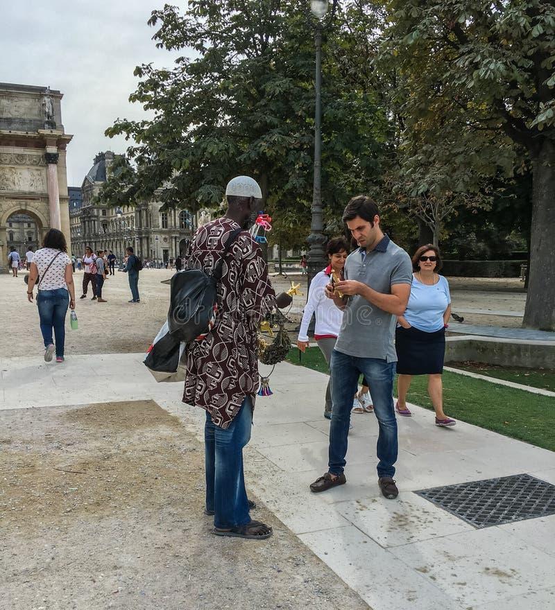 De mens bekijkt herinnering door Afrikaanse verkoper in Tuileries wordt verkocht, Parijs dat royalty-vrije stock foto