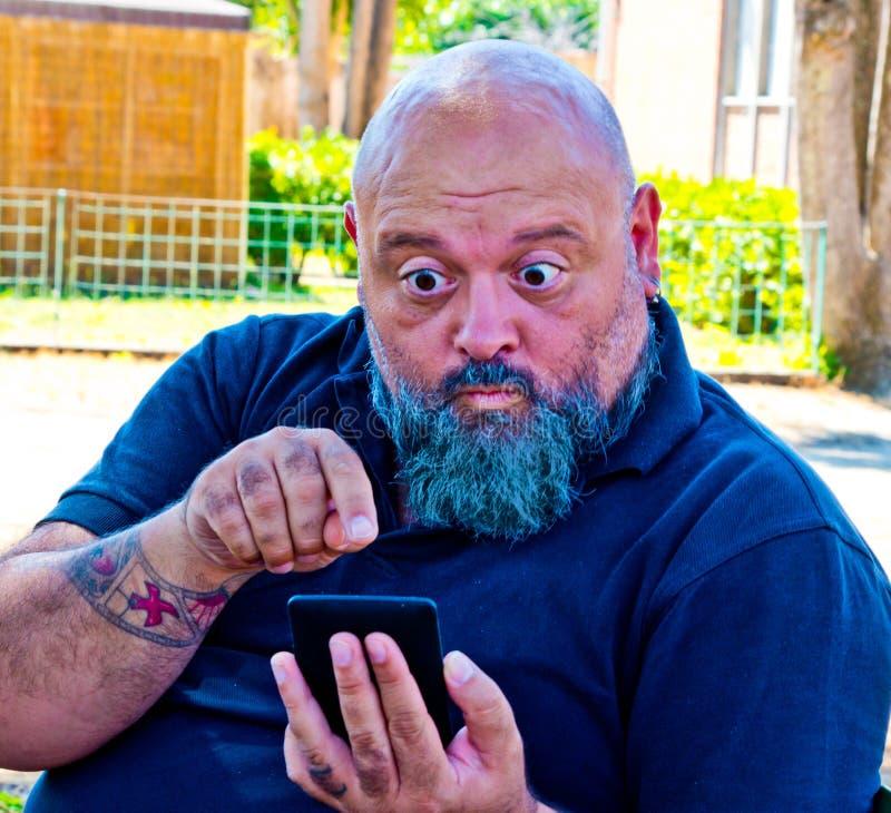 De mens bekijkt verbaasd het nieuws op smartphone stock afbeeldingen