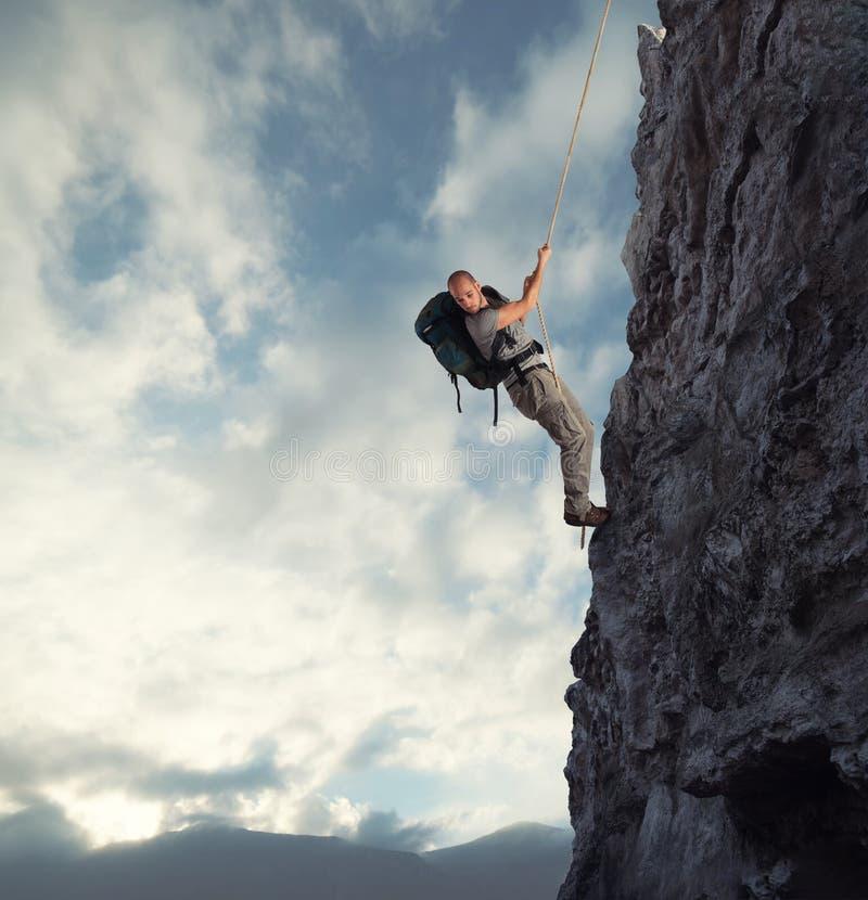 De mens beklimt een hoge gevaarsberg met een kabel stock afbeeldingen