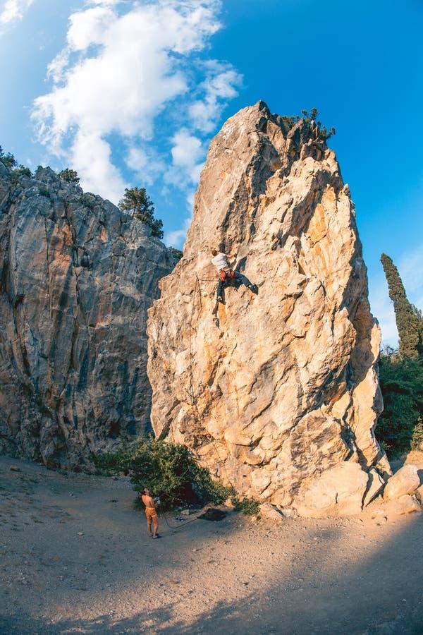 De mens beklimt rots stock afbeelding