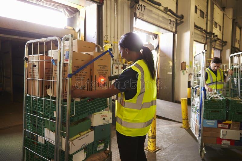De mens bereidt en tast pakketten in een pakhuis voor levering voor af stock foto's