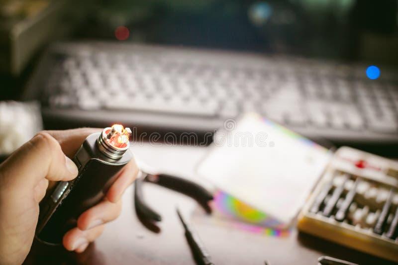De mens bereidt rol het elektronische sap van het roken van sigaretten smakelijke vape voor stock foto