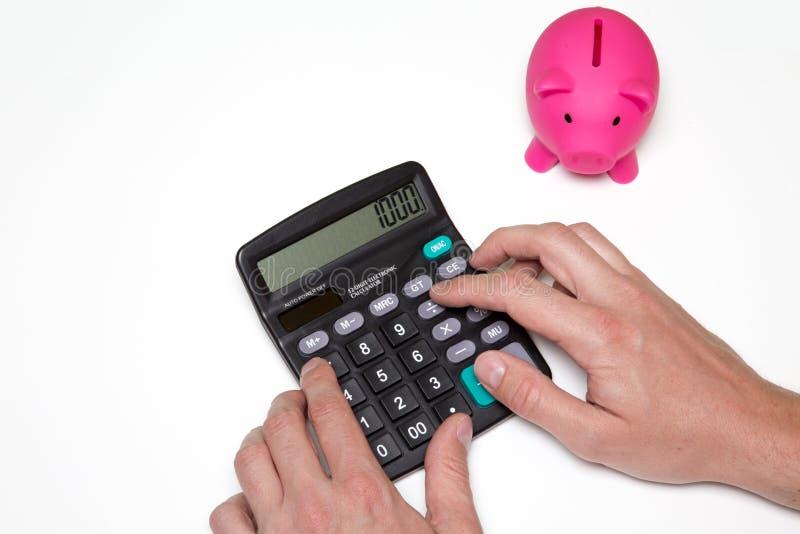 De mens berekent geld De bedrijfsdocumenten van het spaarvarken en op bureau royalty-vrije stock foto's