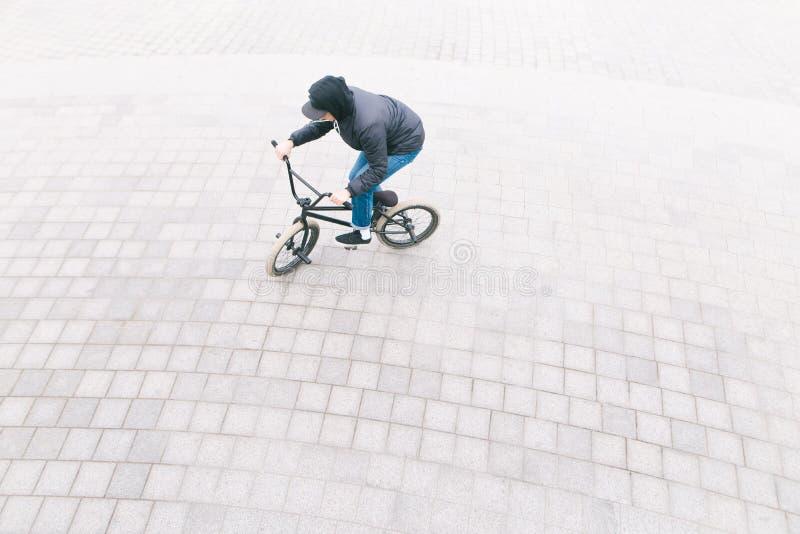 De mens berijdt een BMX-fiets op bestratingsoverheadkosten Minimalistische foto van fietser die op BMX in het vierkant berijdt royalty-vrije stock afbeelding