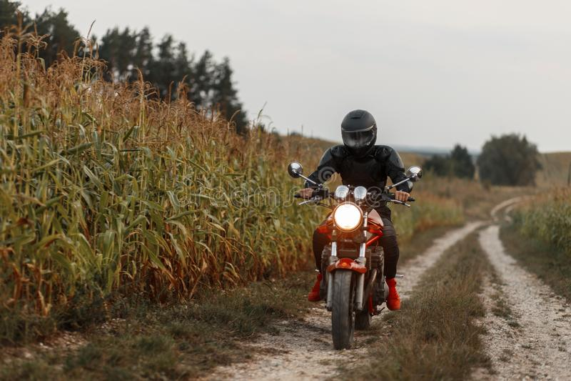 De mens berijdt een motorfiets op het gebied met graan royalty-vrije stock foto