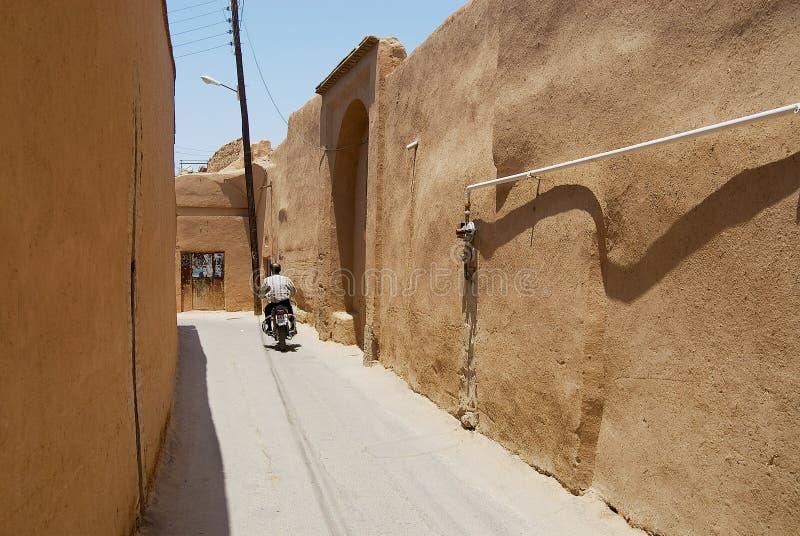 De mens berijdt motor door de smalle straat met klei behandelde muren in het historische deel van Yazd, Iran royalty-vrije stock afbeelding