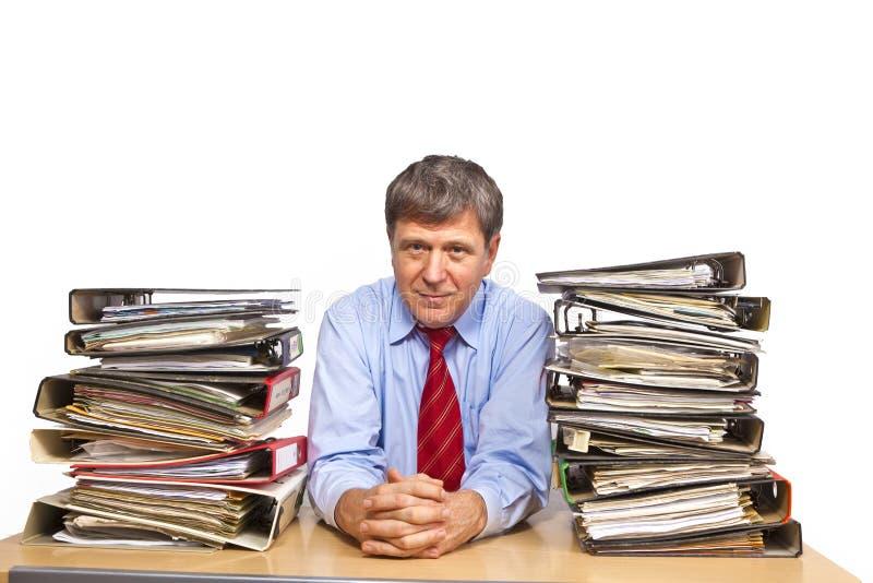De mens bestudeert omslag met dossiers bij zijn bureau stock afbeelding